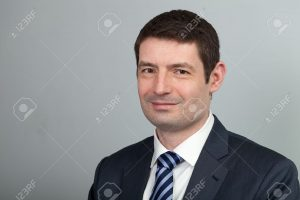 18915078-A-head-and-shoulders-shot-of-a-40-year-old-business-man-in-a-suit-and-shirt-with-blue-tie-Stock-Photo-300x200